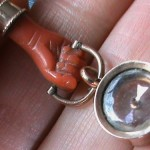 exquisite carved coral hand with compass charm